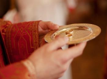 Священник несет кольца для обручения