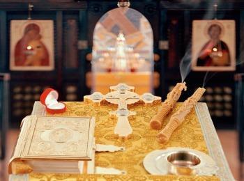 Евангелие, крест, венцы и свечи на аналое
