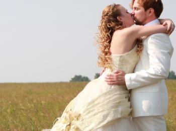 Счастливые повенчанные в светлых нарядах на зеленом поле