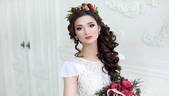 Греческая прическа с алыми цветами на красивой брюнетке