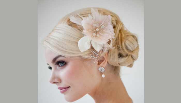 Красивый низкий пучок из светлых волос с нежным цветком