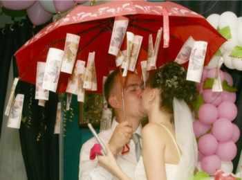 Поцелуй молодоженов под красным зонтиком с подвешенными купюрами