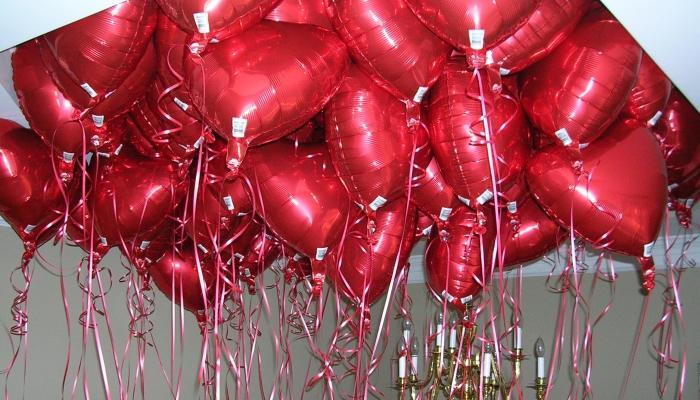 Фольгированные красные шары в форме сердец висят у потолка
