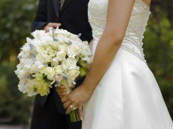 Пышный белый букет в руках у невесты в струящемся платье
