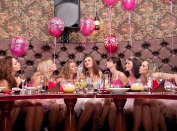 Подружки невесты говорят тосты за столом, украшенным розовыми шариками
