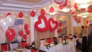 Банкетный зал украшенный красными и белыми шарами для свадьбы