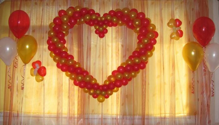 Ровное красно-золотистое сердце из воздушных шариков на шторе