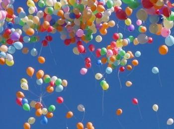 Множество цветных гелиевых шариков взмывают в небо