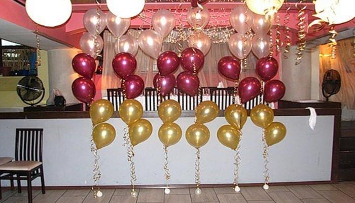 Прозрачные, красные и желтые воздушные шарики у бара на свадебном банкете