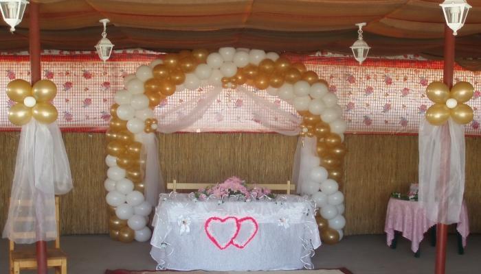 Широкая арка из белых и золотистых шариков, закрепленных над столом для молодоженов