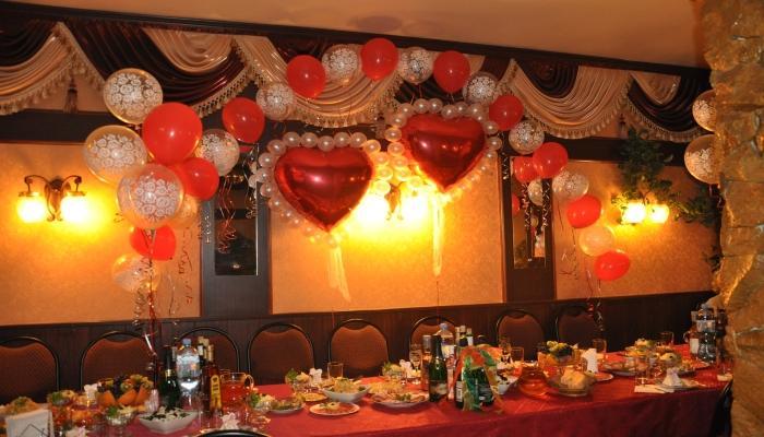 Красивые красные фольгированные шары-сердца над стульями для жениха и невесты