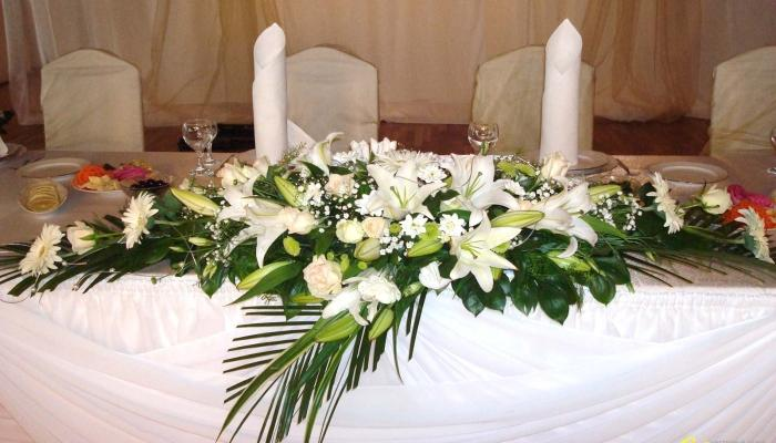 Передний край стола для молодоженов обычно украшают длинной композицией из цветов