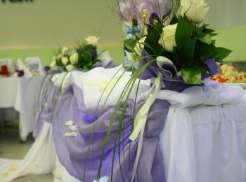 Изящные светло-желтые цветы расставлены вдоль украшенного белой и сиреневой тканью стола