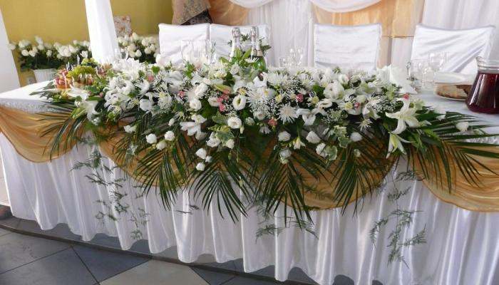 Красивые пастельные и белые цветы с ветвями папоротника украшают стол для жениха и невесты