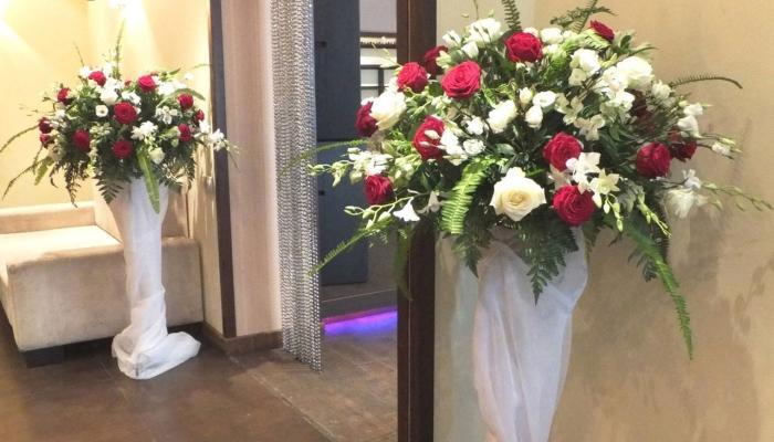 Две высокие вазы с красными и белыми розами у входа в зал