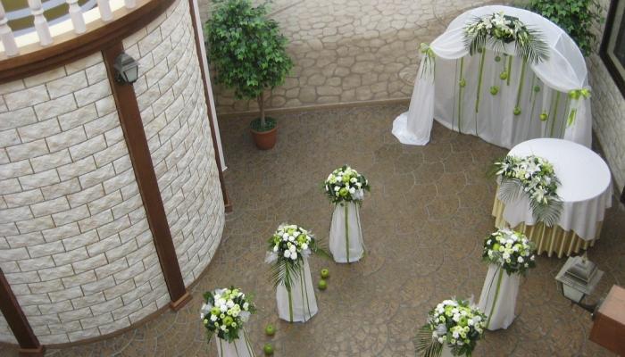 Невысокие колонны с белыми цветами и зелеными листьями перед арочным входом в банкетный зал