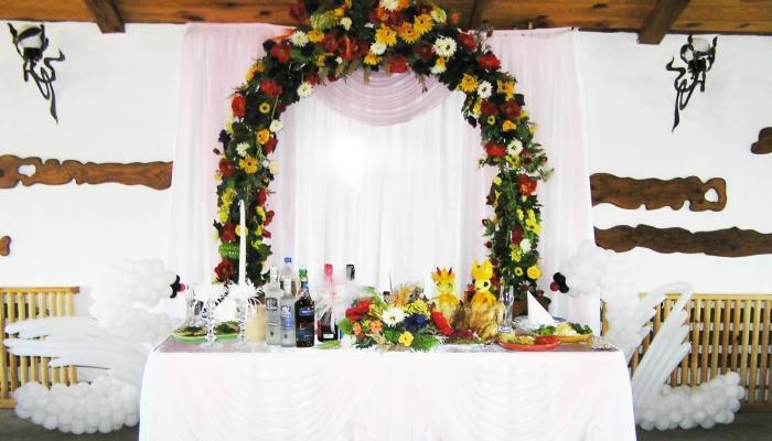 За столом молодоженов можно сделать арку из цветов - это станет отличным местом для фотографирования