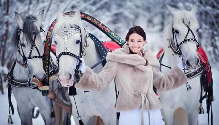 Улыбающаяся невеста в полушубке с тремя лошадьми