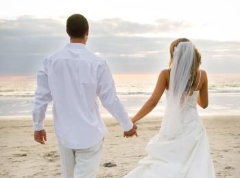 Жених и невеста на песчаном побережье - вид сзади