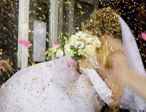 Молодую невесту осыпают лепесточками цветов