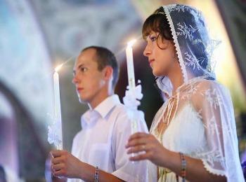 Жених и невеста со свечами во время таинства
