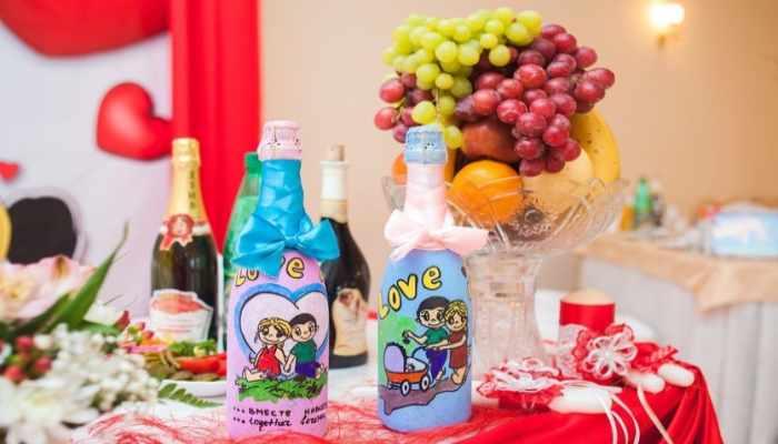 Украшенный яркими цветами стол с бутылками шампанского в стиле Love Is