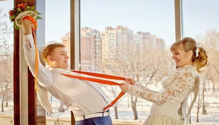 Строгий костюм для жениха с яркими оранжевыми подтяжками и невеста в кружевном платье
