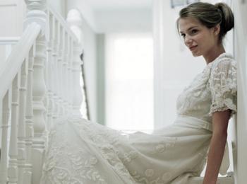 Юная невеста на лестнице в скромном платье с рукавами