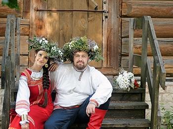 Молодые в зеленых венках и свадебных нарядах с красными элементами