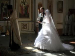 Красивая невеста в закрытом платье с женихом перед священником в церкви