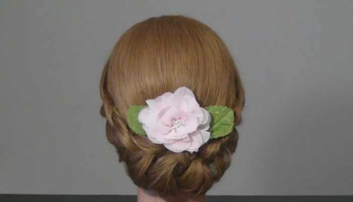 Кокон из русых волос украшенный искусственным цветком
