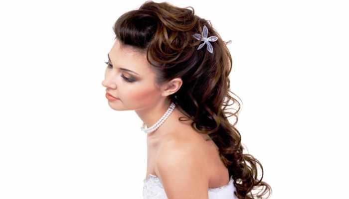 Невеста с пышными кудрявыми волосами украшенными цветами