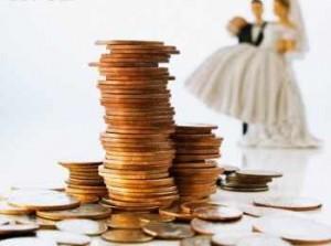 Груда монеток и статуэтка жениха с невестой на дальнем плане