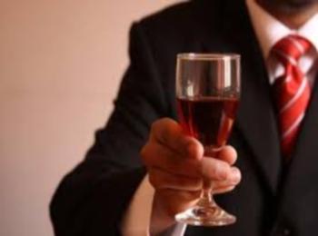 Мужчина с бокалом красного вина в красном галстуке