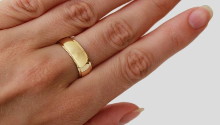 Широкое кольцо из золота выпуклой формы на руке