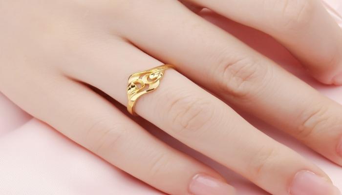 Эффектное позолоченное кольцо ажурной формы на женском пальце