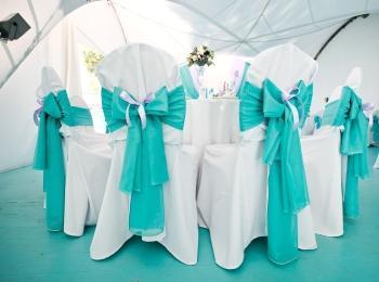 Стулья, украшенные белыми чехлами и бирюзовыми лентами с бантами