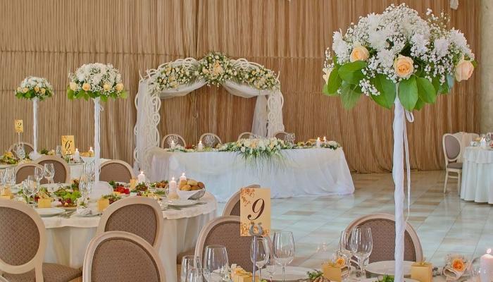Украшение столов для молодоженов и гостей белыми цветами и зелеными листьями