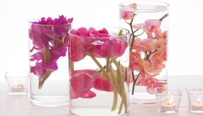 Прозрачные вазы-стаканы с плавающими в воде цветами - необычное украшение свадебного стола