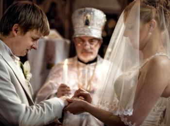Священник венчает молодую пару и молится за их благополучие