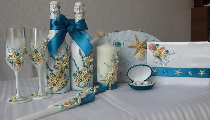Элегантно украшенные по-морскому свечи, бутылки шампанского и другие свадебные аксессуары