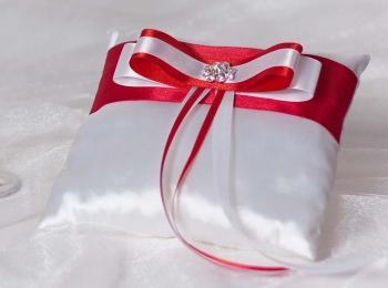 Белая атласная подушка с красной лентой и бантом