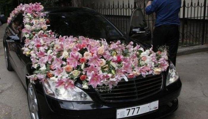 Крупная композиция из белых и розовых орхидей на машине