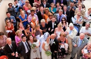 Большая группа гостей поздравляет молодых супругов